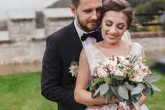 Gorgeous bride with modern bouquet and stylish groom gently hugging and smiling outdoors. Sensual wedding couple embracing. Roman royalty free stock image