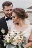 Gorgeous bride with modern bouquet and stylish groom gently hugging and smiling outdoors. Sensual wedding couple embracing. Roman stock image