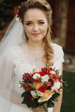 Gorgeous bride smiling and holding wedding bouquet of red roses. Orchids. stylish wedding couple posing outdoors. tender sensual moment. floral arrangements Royalty Free Stock Images