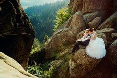 Gorgeous bride is softly hugging the smiling glamour groom back while sitting on the rock at the background of the Royalty Free Stock Photo