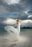 Gorgeous bride standing and posing under threatening clouds at s Royalty Free Stock Images