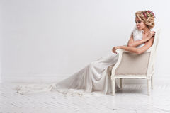 Gorgeous bride standing on sofa Stock Photos