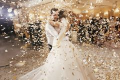 Gorgeous bride and stylish groom dancing under golden confetti a. T wedding reception. Happy wedding couple performing first dance in restaurant. Romantic stock image