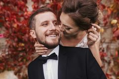 Gorgeous bride and stylish groom gently hugging and smiling at w. All of autumn red leaves. Happy sensual wedding couple embracing. Romantic moments of newlywed royalty free stock photo