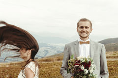 Gorgeous bride and stylish groom  having fun, boho wedding, luxu. Ry ceremony at mountains Stock Photography
