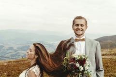 Gorgeous bride and stylish groom  having fun, boho wedding, luxu. Ry ceremony at mountains Stock Images
