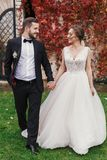Gorgeous bride and stylish groom holding hands and walking at wa. Ll of autumn red leaves. Happy Sensual wedding couple smiling. Romantic moments of newlyweds stock photography