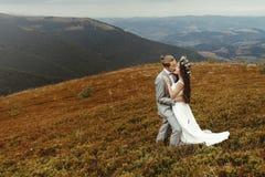 Gorgeous bride and stylish groom hugging,  boho wedding couple, Stock Image