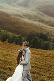 Gorgeous bride and stylish groom hugging at sunny landscape,  bo Royalty Free Stock Photo