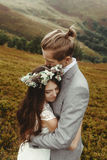 Gorgeous bride and stylish groom hugging at sunny landscape,  bo Stock Photography