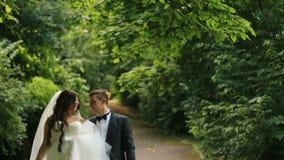Gorgeous bride walks with her elegant groom walks on sunny summer park full of green leaves stock video