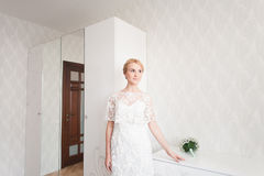 Gorgeous bride with wedding bouquet makeup and hairstyle in bridal dress at home waiting for groom. Royalty Free Stock Photography