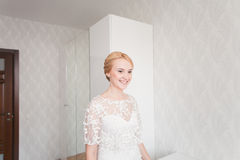 Gorgeous bride with wedding bouquet makeup and hairstyle in bridal dress at home waiting for groom. Stock Photography