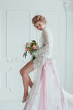Gorgeous bride with wedding bouquet sitting on the decorated ladder.  Royalty Free Stock Photos