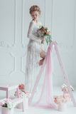 Gorgeous bride with wedding bouquet standing on the decorated ladder. Look down Stock Photos
