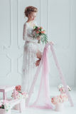 Gorgeous bride with wedding bouquet standing on the decorated ladder. Look down Stock Photo