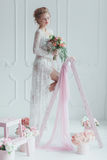 Gorgeous bride with wedding bouquet standing on the decorated ladder. Young woman looks out the window.  Stock Images
