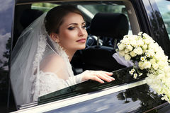 Gorgeous bride in wedding dress with bouquet of flowers posing in car. Fashion outdoor photo of gorgeous bride in wedding dress with bouquet of flowers posing in Stock Photography
