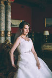 Gorgeous bride in wedding dress in luxury interior with diamond jewelry posing at home and waiting for groom Stock Photos