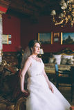 Gorgeous bride in wedding dress in luxury interior with diamond jewelry posing at home and waiting for groom Royalty Free Stock Image