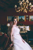 Gorgeous bride in wedding dress in luxury interior with diamond jewelry posing at home and waiting for groom Royalty Free Stock Images