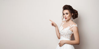 Gorgeous bride in wedding dress shocked looking at camera and gesturing by finger at side. Brunette woman with stylish haircut pos Royalty Free Stock Photography