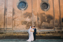 Gorgeous bride in white dress and handsome groom holding bridal bouquet face-to-face near brown wall of old church Stock Photo