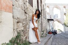 Gorgeous bride in white dress near greece city, showing his legs, poses near white stone wall in street in summer time. stock image