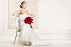 Gorgeous bride with white dress with red flowers bouquet Royalty Free Stock Photo