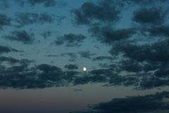 Gorgeous bright moon and few clouds on dark blue night sky. Amazing nature background.  stock images