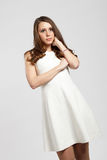 Gorgeous brown hair teenage girl. Gorgeous shy brown hair teenage girl dressed in white royalty free stock photos