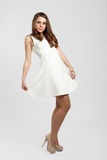 Gorgeous brown hair teenage girl. Dressed in white pulling her dress Stock Images