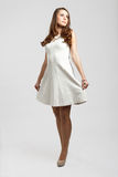 Gorgeous brown hair teenage girl. Dressed in white pulling her dress Royalty Free Stock Photo