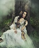 Gorgeous brunette. Beauty in a old-fashioned dress in a forest stock image