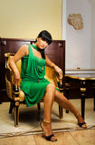 Gorgeous brunette. Sitting on a golden chair Stock Photography