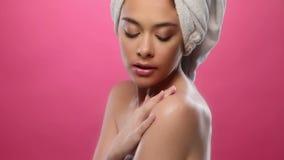 Gorgeous brunette in bathrobe moisturising stock video footage