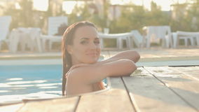 Gorgeous brunette in a bikini swimming in the pool. Gorgeous brunette in bikini swimming in the pool outside with delight stock footage