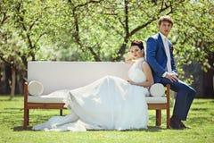 Gorgeous brunette bride & groom posing in park on white sofa Stock Photos