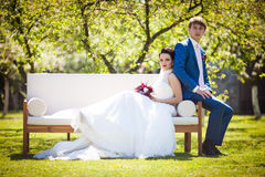Gorgeous brunette bride & groom posing in park on white sofa royalty free stock photography