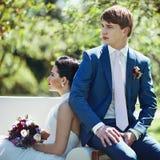 Gorgeous brunette bride & groom posing in park on white sofa Stock Photo