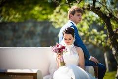 Gorgeous brunette bride & groom posing in park on white sofa stock images