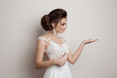 Gorgeous brunette bride holding something on hand, gesturing super sign by big finger and showing by hand to side. Female wearing Stock Photos