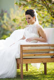 Gorgeous brunette bride posing in park on white luxury sofa royalty free stock photography