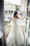 Gorgeous brunette bride in sexy wedding dress posing on balcony. City in the background Stock Photo