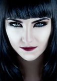 Gorgeous brunette with dark makeup and white skin. Smirking Stock Image