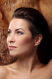 Gorgeous brunette with fur on a background Stock Images