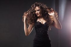 Gorgeous brunette girl in elegant black dress. Beautiful long curly hair. royalty free stock photo