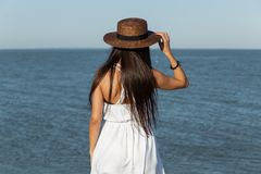 Gorgeous brunette girl with long hair in white dress and brown hat stand near the sea on a sunny day. stock images