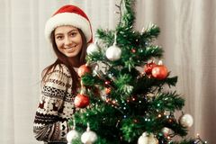 Gorgeous brunette girl in red santa claus hat and cozy reindeer Stock Photos