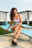 Gorgeous brunette girl with sexy long legs. Wearing black heels sitting on pool chair in bright sunny day Stock Photos